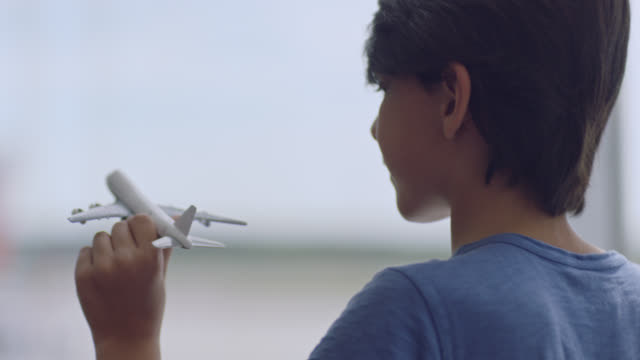 SLO MO. CU. Young boy plays with toy airplane near gate window in airport terminal.