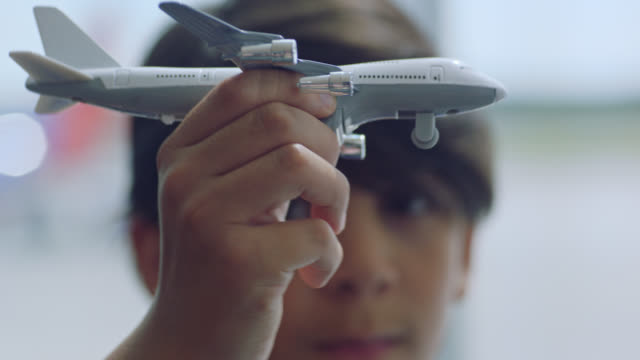 SLO MO. ECU. Young boy plays with toy model commuter airplane.