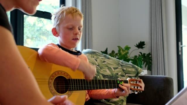 若い男の子は彼の音楽の先生との電話会議を通して彼のギターを練習します - アコースティックギター点の映像素材/bロール