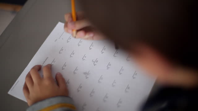 a young boy practices long division on a worksheet in class. - 男児1人点の映像素材/bロール