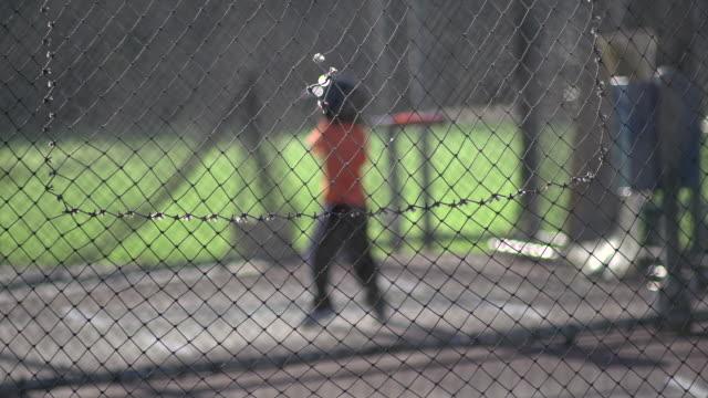 a young boy practicing baseball at the batting cages.  - slow motion - gabbia di battuta video stock e b–roll