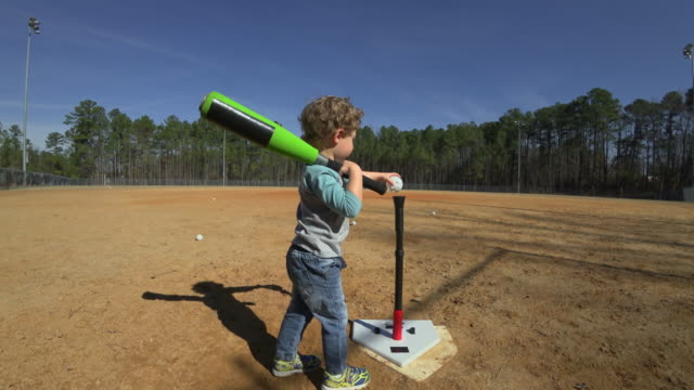 young boy practicing batting on an empty baseball field - fallimento video stock e b–roll