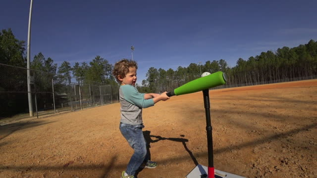 young boy practicing batting on an empty baseball field - baseball bat stock videos & royalty-free footage