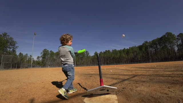 young boy practicing batting on an empty baseball field - batting stock videos & royalty-free footage