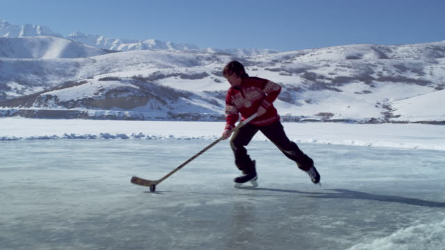young boy practicing hockey at an outdoor ice rink. - pond stock videos and b-roll footage