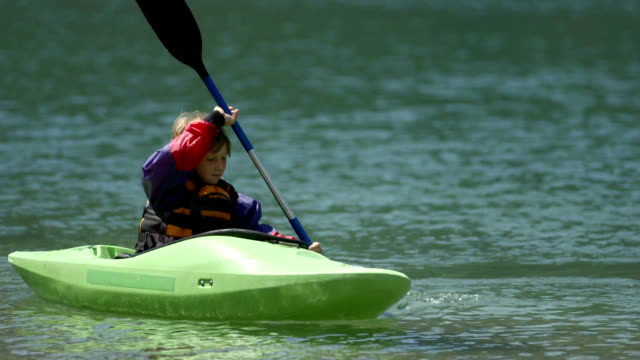 hd: young boy practicing paddling in a kayak - elementary age stock videos & royalty-free footage