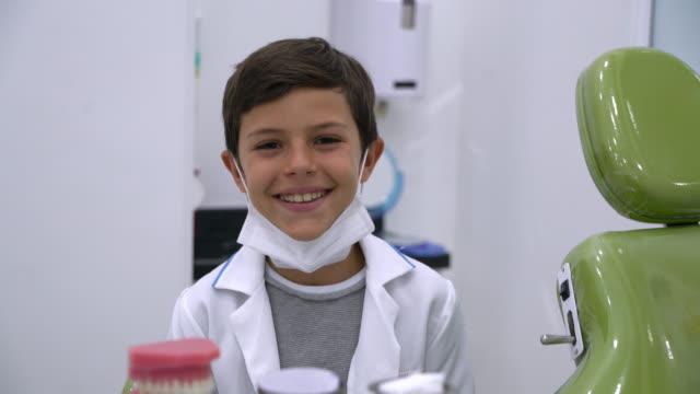 vídeos de stock, filmes e b-roll de menino novo que finge ser um dentista que olha a câmera que sorri - dentista