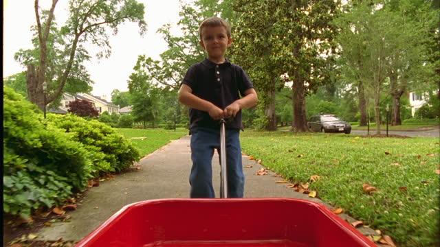 A young boy pulls a red wagon through his suburban neighborhood.