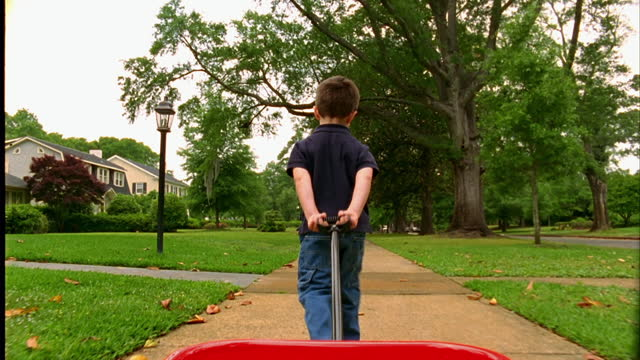 stockvideo's en b-roll-footage met a young boy pulls a red wagon through his suburban neighborhood. - speelgoed