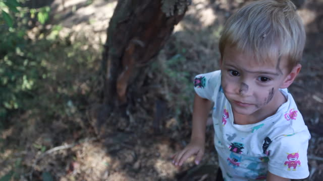 vidéos et rushes de young boy pulls bark off of a tree and points it at the camera on a hot summer day - kelly mason videos