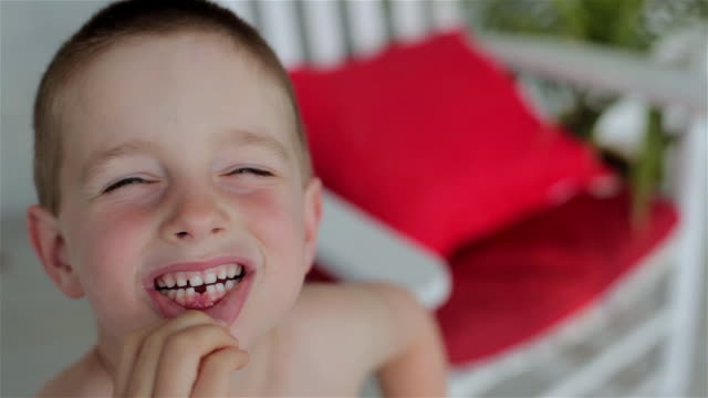 a young boy pulls down his lower lip to show his missing front tooth while smiling - menschlicher zahn stock-videos und b-roll-filmmaterial