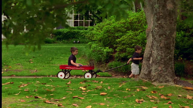 vídeos de stock e filmes b-roll de a young boy pulls his big brother through their neighborhood in a red wagon. - irmão