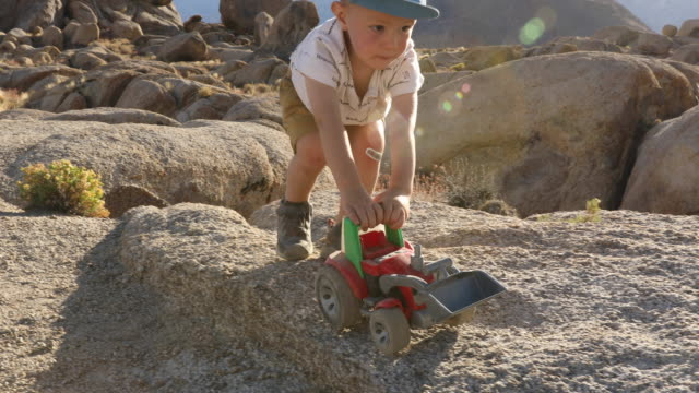 a young boy pushing his truck around the rocks while camping. - one boy only stock videos & royalty-free footage