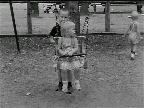 vídeos de stock e filmes b-roll de b/w 1955 young boy pushing small girl on swing - fazer um favor