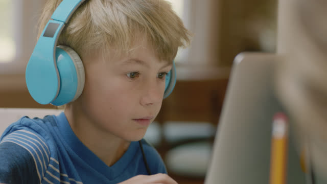 cu young boy puts on headphones, begins typing on laptop. - blue stock videos & royalty-free footage