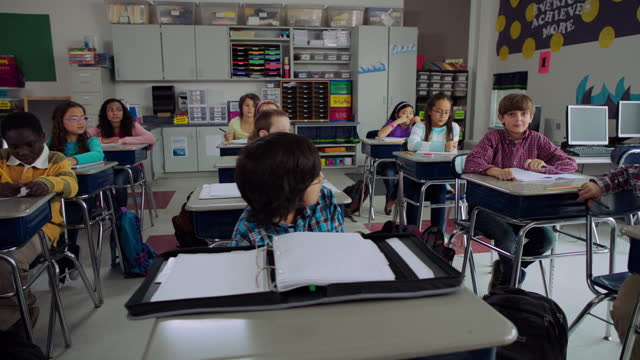 a young boy raises his hand and answers a question during class. - educazione primaria video stock e b–roll