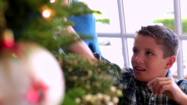 Young boy reaches up to hang ornament on Christmas tree