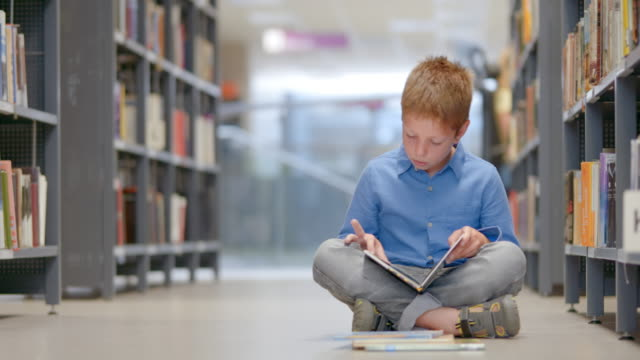 ds young boy reading a book sitting in library aisle - cross legged stock videos & royalty-free footage