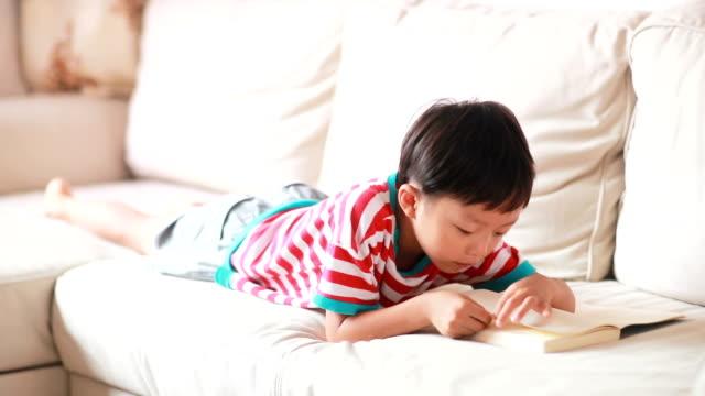 stockvideo's en b-roll-footage met jonge jongen lezen van een boek - barefoot
