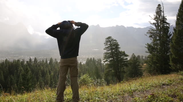 Young boy removes hood after rain; he looks out across mountains and forest
