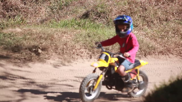 vidéos et rushes de young boy rides a dirt bike around a bend and over a small hill on a dirt bike track - kelly mason videos