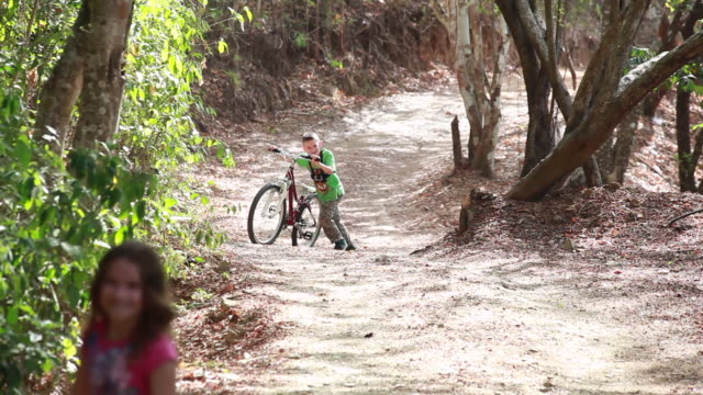 young boy rides bicycle along country road and then gets off and walks half of the distance with young girl in the foreground - kelly mason videos stock videos & royalty-free footage
