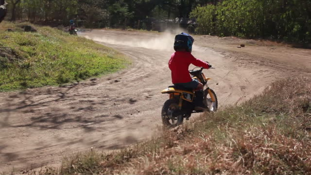 young boy rides dirt bike around a bend while another young boy follows him on a dirt bike track - kelly mason videos stock videos & royalty-free footage