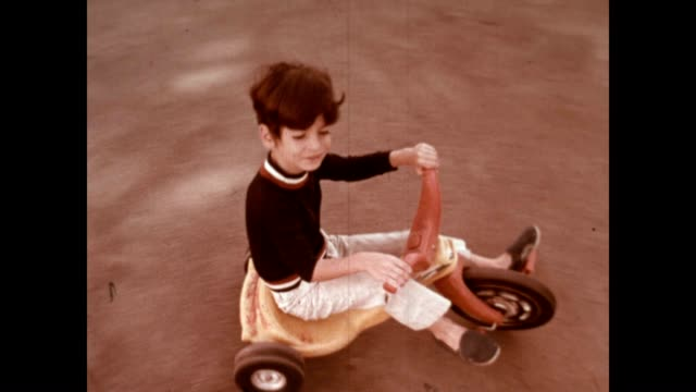 a young boy rides his plastic big wheel bike in the late 1970's - tricycle stock videos and b-roll footage