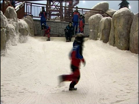 Young boy rides sled down slope at world's largest indoor ski resort Ski Dubai