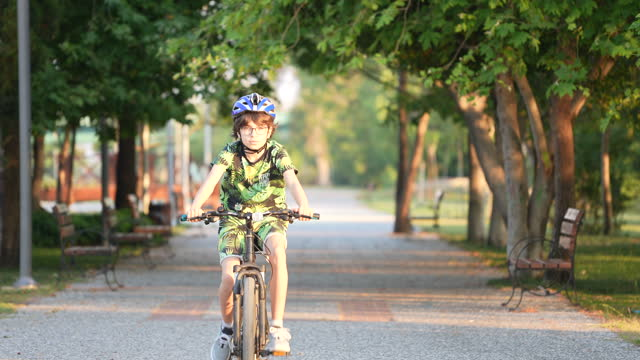 young boy riding a bike on a sunny day at park. - recreational pursuit stock videos & royalty-free footage