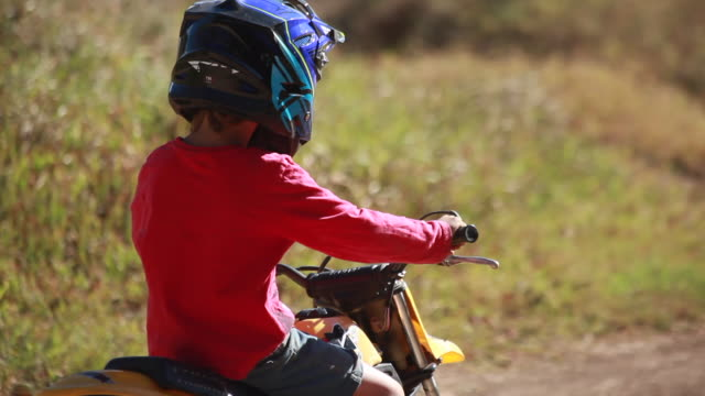 young boy riding a dirt bike around a bend while a woman on a dirt bike follows him on a dirt bike track - kelly mason videos stock videos & royalty-free footage