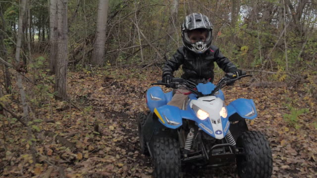young boy riding atv through forest - quadbike stock videos & royalty-free footage