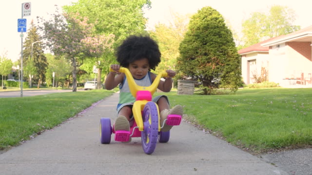 young boy riding big wheel pedal car down sidewalk - tricycle stock videos & royalty-free footage