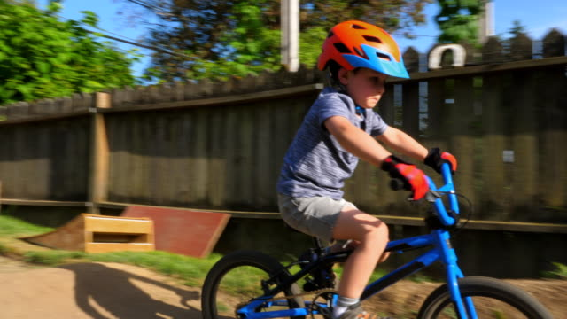 pan r/f young boy riding bmx bike on backyard dirt track on summer evening - sicurezza sul posto di lavoro video stock e b–roll