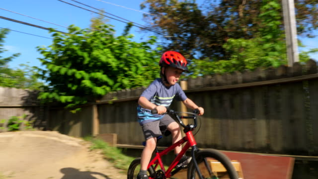 vidéos et rushes de pan young boy riding bmx bike on dirt track in backyard on summer evening - casque de vélo