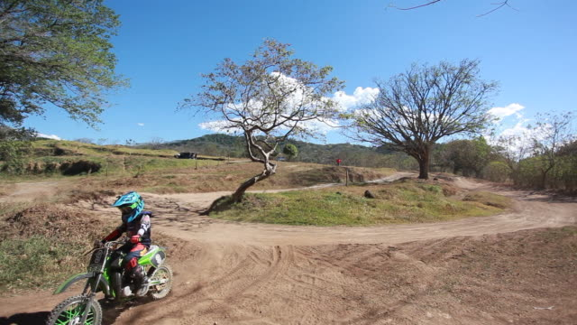 vidéos et rushes de young boy riding dirt bike around a bend and off of the dirt bike track on a sunny summer day - kelly mason videos