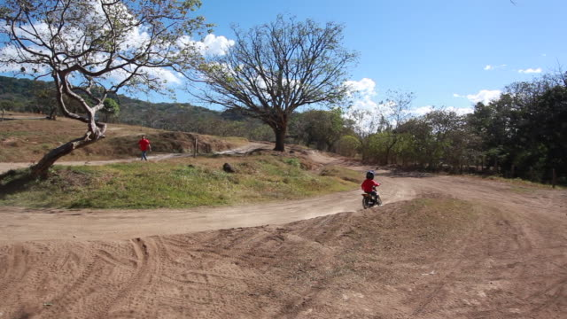 young boy riding dirt bike around a bend on a dirt bike track while a woman chases him on foot - kelly mason videos stock videos & royalty-free footage