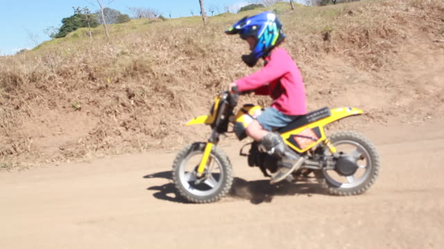vídeos de stock e filmes b-roll de young boy riding dirt bike around a bend on a track then down a hill while mom watches on a dirt bike track - kelly mason videos