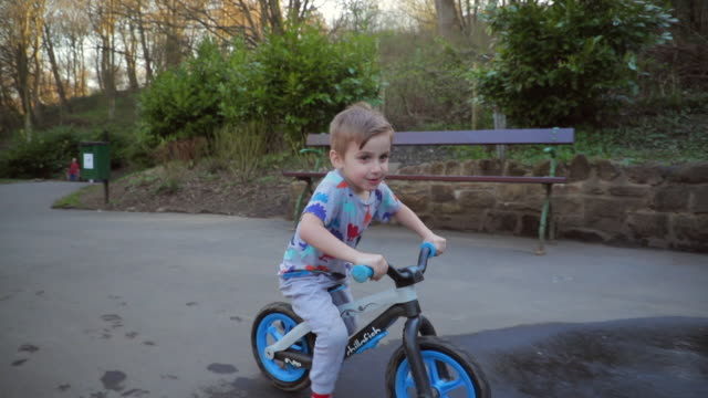 young boy riding his bicycle through the park - western europe stock videos & royalty-free footage