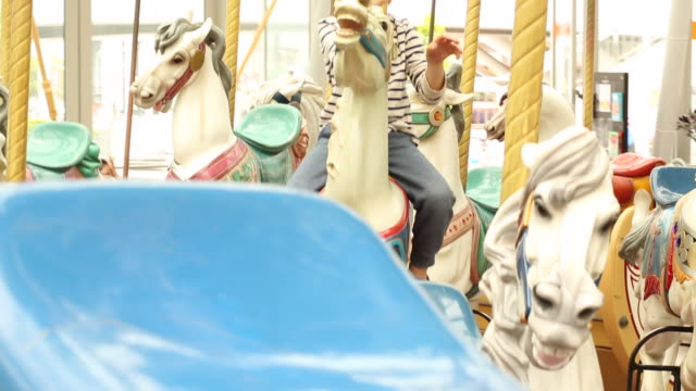 a young boy riding on a carousel indoors smiling and having fun. - carousel horse stock videos and b-roll footage