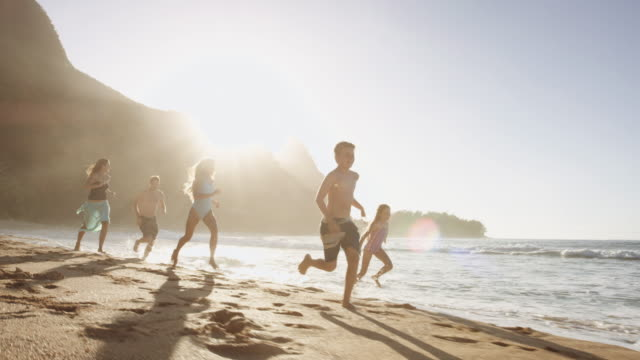 Young boy running along beach as family follows