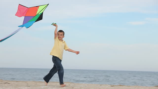 young boy running and flying kite on beach - kite toy stock videos and b-roll footage