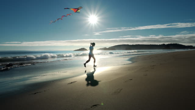 young boy running and flying kite on pacific ocean beach, oregon - joy stock videos & royalty-free footage