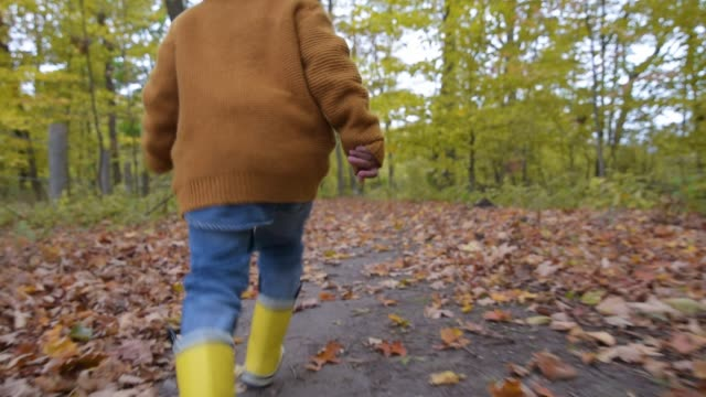 young boy running down path. - ein junge in gummistiefel stock-videos und b-roll-filmmaterial