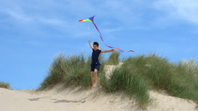 A young boy Running leaps from sand dunes Flying his Kite.