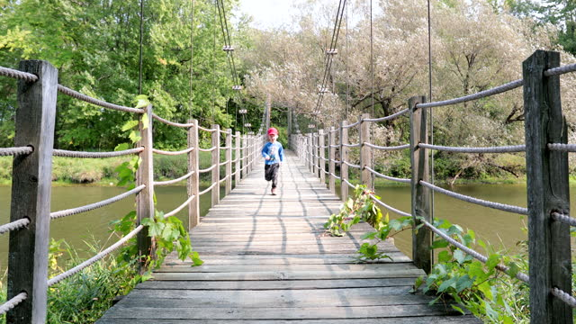 young boy running on suspension bridge in summer - parc national stock videos & royalty-free footage
