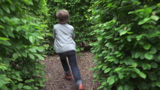 a young boy running through a hedge maze - maze stock videos & royalty-free footage