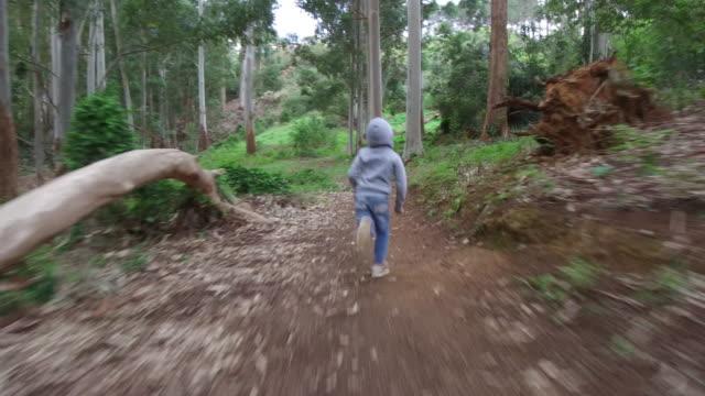 stockvideo's en b-roll-footage met jonge jongen loopt door een weelderig groen bos - volgen activiteit