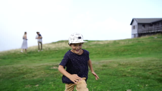 vidéos et rushes de jeune garçon qui traverse le terrain gazonné sur le dessus de la montagne - casquette