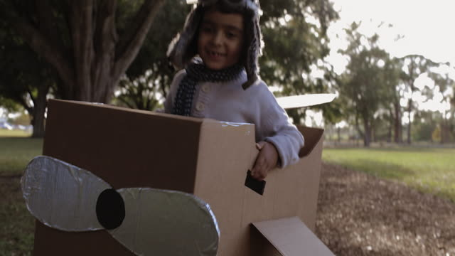 ts cu young boy running towards camera in cardboard aeroplane dressed as a pilot - flying goggles stock videos and b-roll footage